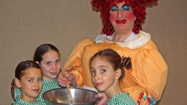 Richard Hunter as Dame Fanny the Cook with Tilda Fletcher,Savi Pachos and Isabel Tate.